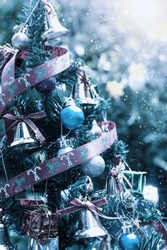 Decorated Christmas tree in winter color tone with blurred background.