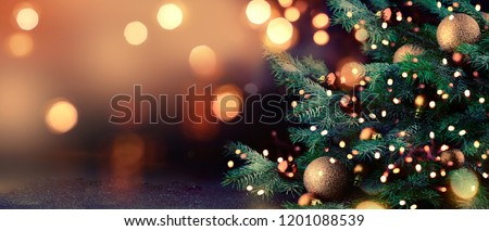 Stock Photo Decorated Christmas tree on blurred background.