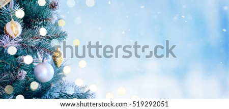 Decorated Christmas tree with bright bokeh on winter blue snowy background. Christmas banner.