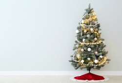 Decorated Christmas tree with red skirt indoors, space for text
