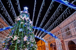 Decorated Christmas tunnel with lights and Christmas tree in the night street of the city