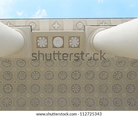 Decorated classical architecture building ceiling with columns fragment on blue sky background