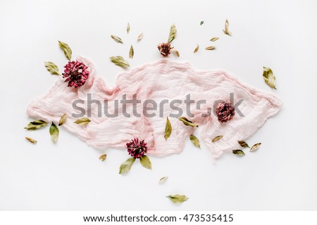 decorated composition with dry red roses, petals and pink textile on white background. flat lay, top view