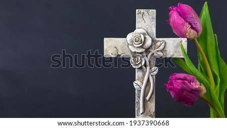 Decorated cross with a purple tulip flowers on a dark background. Condolence card. Plenty of copy space for religious sayings. Funeral and mourning concept. Photo stock ©