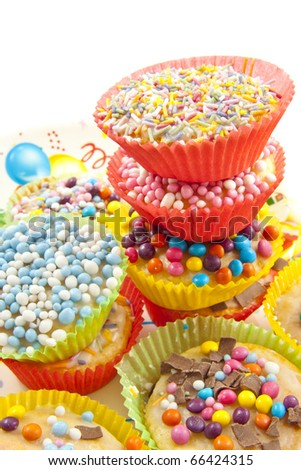 Decorated cup cakes on a pile ready to treat