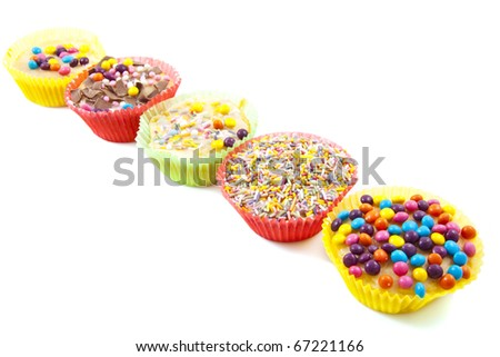 Decorated cupcakes in a row isolated over white