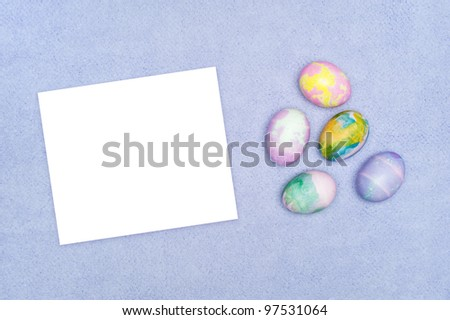 Decorated Easter eggs on purple cloth with a blank white card for placement of copy.