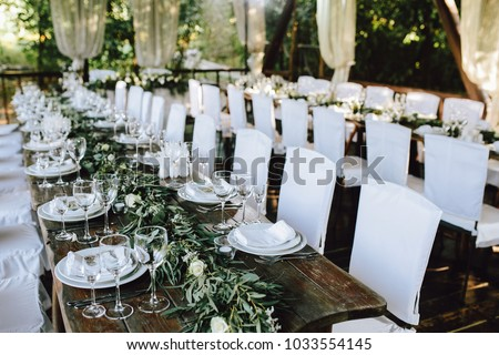 Decorated elegant wooden wedding table for banquet outdoor in garden, in the style of rustic with eucalyptus and flowers, porcelain plates, glasses, white chairs. Horizontal