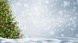 decorated fir tree in snowy landscape, beautiful christmas tree with red balls on abstract winter background with advertising space, white snowflakes in front of the silver sky