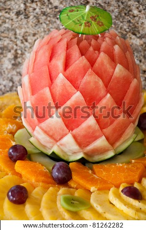 decorated fruit table setting with watermelon, grapes, orange and pineapple slices