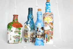Decorated glass bottles by covering in decoupage on the white background