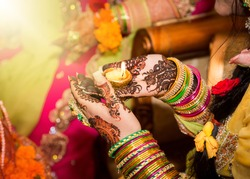 Decorated Indian bride holding candle in her hand. Focus on Hand.