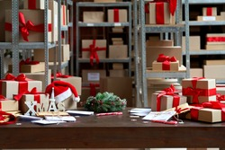 Decorated Merry Christmas table with gifts boxes in warehouse interior background. Many presents wrapped with red ribbons and letters on desk in storage. Xmas postal shipping delivery concept.