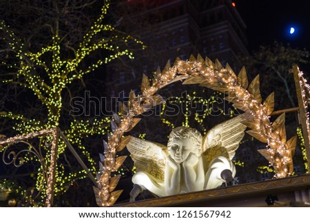 Decorated ornament of angel or cupid figure on the booth at Christmas Market in Germany and background of illuminated light on the tree at night. #1261567942
