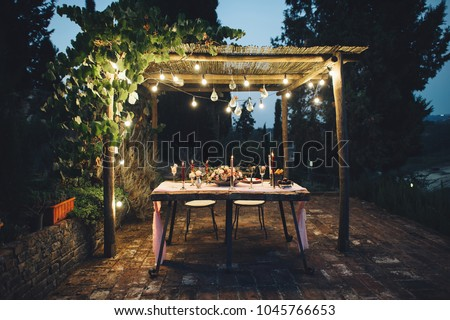 Decorated outdoor wedding table with flowers, lights and candles in rustic style