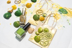 Decorated paper bags to give away. Collage with shells and wooden gears painted with gold and green nail polish. Beach-themed crafts.