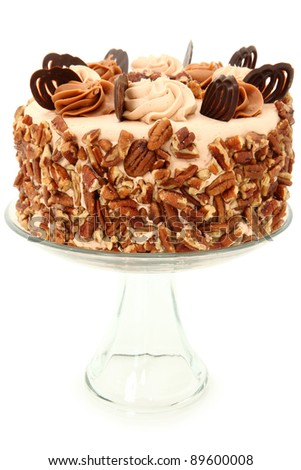 Decorated Pecan Caramel Chocolate Cake on Glass Display Platter over White Background