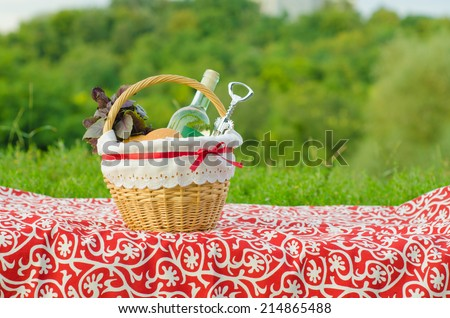 Decorated picnic basket with a bottle of white wine, corkscrew, buns and bunch of basil on red tablecloth, green landscape