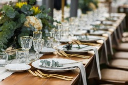Decorated plate with fork and spoon. Table set up in boho style with pampas grass and greenery
