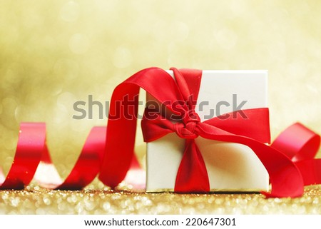 Decorated present in white box with red ribbon on golden background #220647301