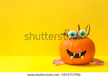 Decorated pumpkin with candy eyes on yellow background Stock photo ©