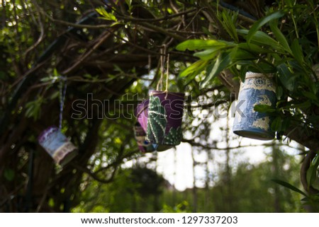 Decorated recycled tin cans made into plant pots hanging from trees.  Crafting, recycling, childrens gardening concepts.