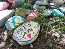 Decorated rocks that state Keep Safe in a woodland area, decorated by local children during the covid 19 coronavirus pandemic. Arts and crafts are a good way of keeping children busy during this time