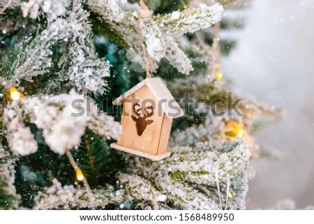 Decorated snow-covered Christmas tree close-up. Wooden toy house illuminated garland. Christmas baubles Macro photo with bokeh. concept winter holiday light decorations. new year 2020 free space text #1568489950