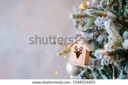 Decorated snow-covered Christmas tree close-up. Wooden toy house illuminated garland. Christmas baubles Macro photo with bokeh. concept winter holiday light decorations. new year 2020 free space text #1568556805