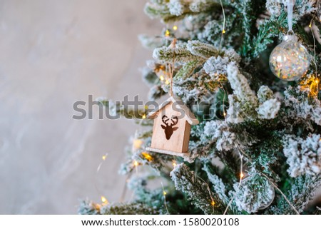 Decorated snow-covered Christmas tree close-up. Wooden toy house illuminated garland. Christmas baubles Macro photo with bokeh. concept winter holiday light decorations. new year 2020 free space text #1580020108