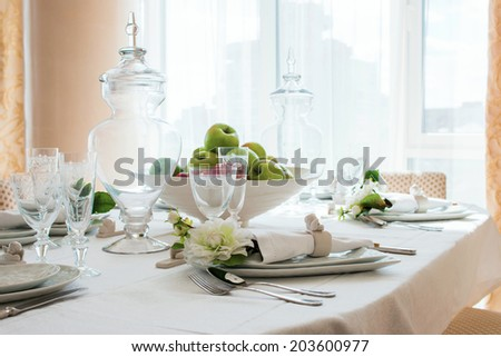 decorated table by the window in the dining room with apples