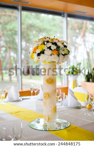 decorated table in the restaurant at the wedding, bouquet, Bouquet of yellow flowers.