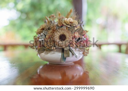 Decorated   vase  with dried flowers of all kinds  on  dinner  table.