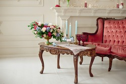 Decorated vintage table in white baroque style interior with red luxury sofa. Table is set for romantic event.