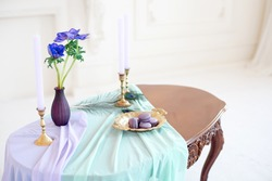 Decorated vintage table in white baroque style room with colored tablecloth and pillows. Luxury vintage Items like vases, candles, jug, tray are decorating the table.