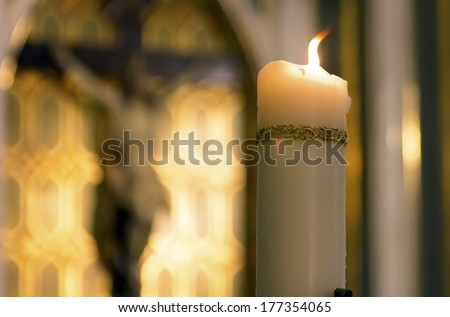 decorated white candle burning inside a Catholic with the image of Christ behind Church