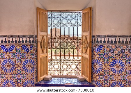 decorated window with mosaics and outside view on kasbah, ouarzazate