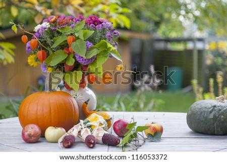 decorated wooden garden table at the terrace, with a selfmade clay vase with a flower bouquet, pumpkins, apples.