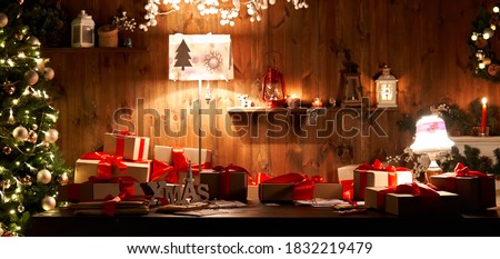 Decorated xmas table with Merry Christmas gifts in cozy Santa home interior, banner. Happy New Year presents boxes in workshop late in night with lights on xmas tree, holiday eve background.