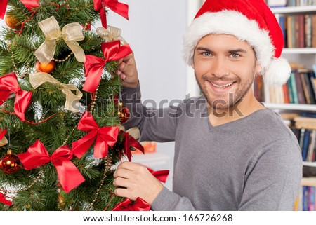 Decorating a Christmas tree. Cheerful young man decorating a Christmas tree and smiling at camera
