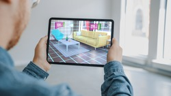 Decorating Apartment: Man Holding Digital Tablet with AR Interior Design Software Chooses 3D Furniture for Home from Online Shop with Shown Prices. Over Shoulder Screen Shot with 3D Render