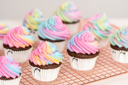 Decorating chocolate unicorn cupcakes with colorful buttercream icing and sprinkles.