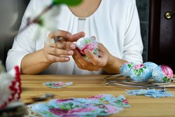 Decorating Easter eggs with decoupage technique. Girl holding a brush and an egg to stick a napkin