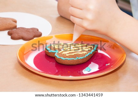 Decorating gingerbread cookies with icing, preparations for the holiday
