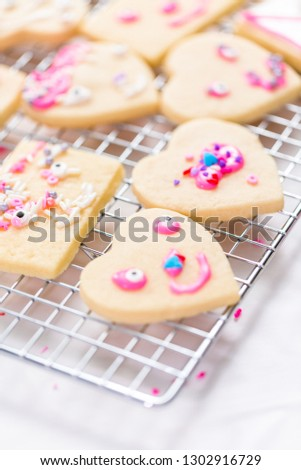 Decorating heart shape sugar cookies with royal icing and pink sprinkles for Valentine's day.