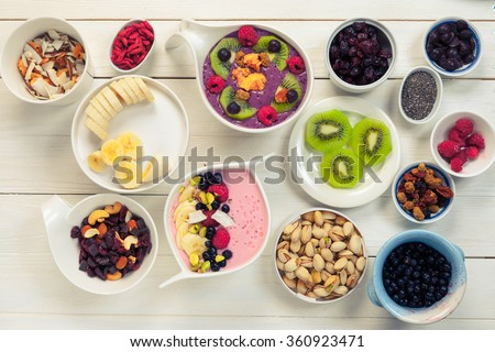 Decorating of Pink strawberry and blue acai berries smoothie bowl with superfood ingredients, Clean eating breakfast concept, top view, white wooden table, rustic style