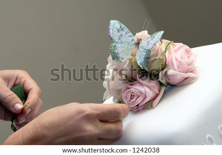 Decorating white wedding cake with roses and butterfly.