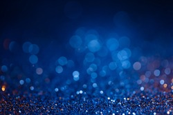 Decoration bokeh glitters background, abstract shiny backdrop with circles,modern design overlay with sparkling glimmers. Blue and golden backdrop glittering sparks with blur effect