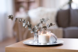 decoration, hygge and cosiness concept - burning white fragrance candle on tray and branches of eucalyptus populus on table at cozy home