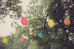 Decoration, illumination, electricity, holidays and lightning concept - close up of electric bulb garland and balloons hanging in summer garden, vintage retro style